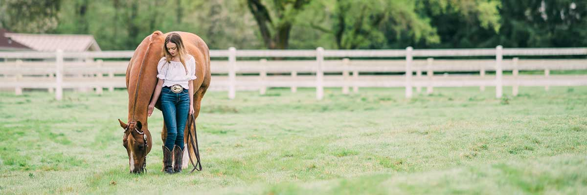 young-girl-with-horse-grazing-in-pasture